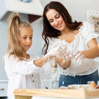 Moeder en dochter die deeg voorbereiden