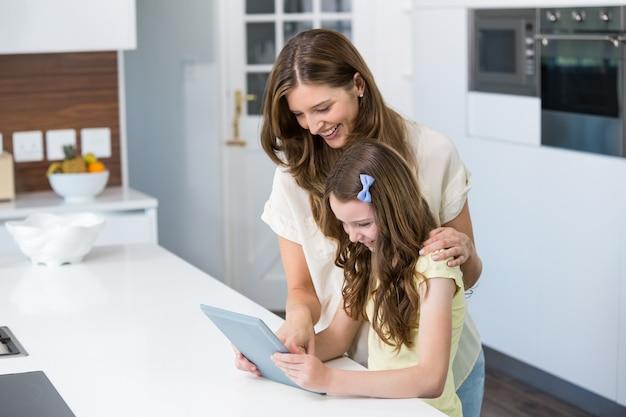 Moeder en dochter die digitale tablet gebruiken