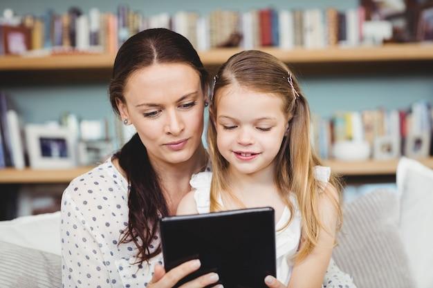 Moeder en dochter die digitale tablet op bank thuis gebruiken