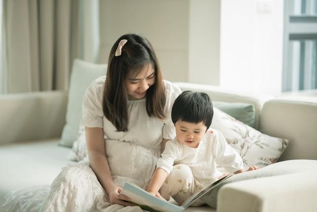Moeder en dochter die een boek in de woonkamer lezen