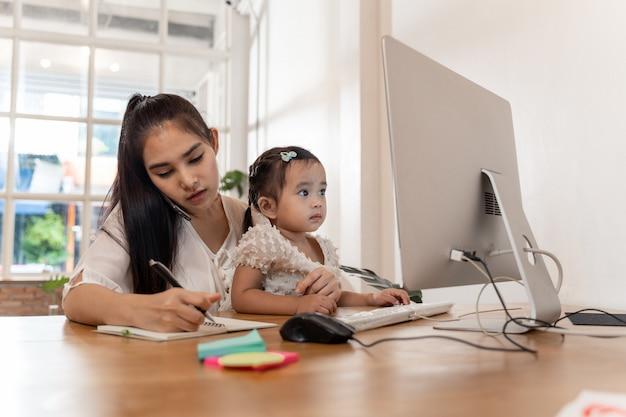 Moeder en dochter die een computer met behulp van terwijl het werken vanuit huis