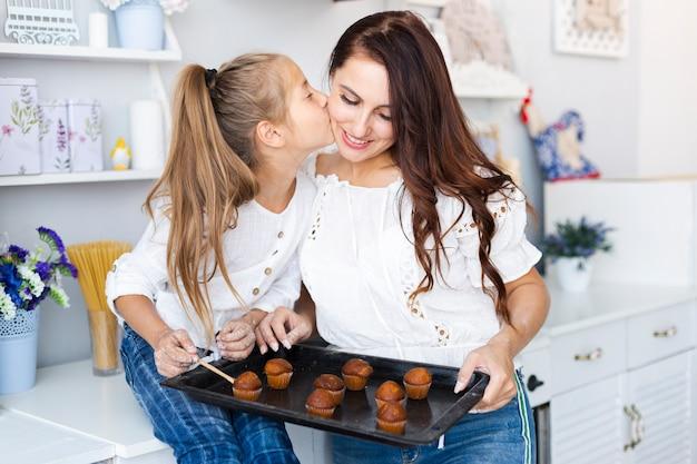 Moeder en dochter die een dienblad met muffins houden