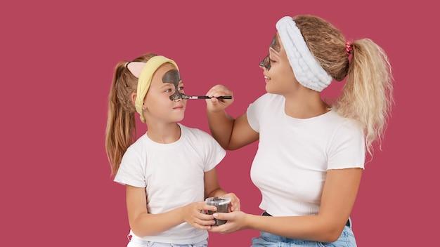 Moeder en dochter die een kleimasker doen voor de huidzorg van de gezichtsfamilie op geïsoleerd rood