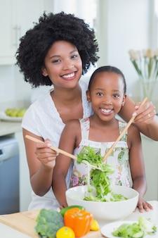 Moeder en dochter die een salade samen maken