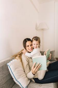 Moeder en dochter die en boek koesteren lezen