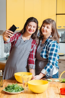 Moeder en dochter die en in keuken glimlachen stellen