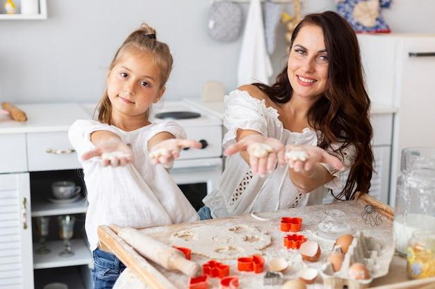 Moeder en dochter die gemaakte koekjesvormen tonen