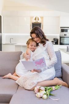Moeder en dochter die groetkaart samen op bank thuis lezen