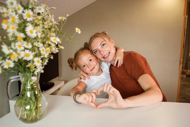 Moeder en dochter die hartsymbool met hun handen tonen.