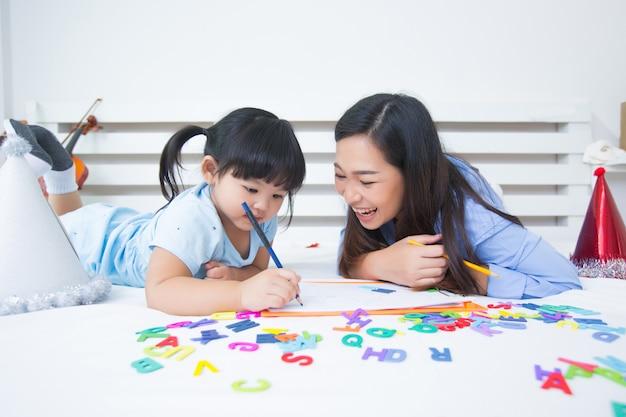 Moeder en dochter die het alfabet bestuderen