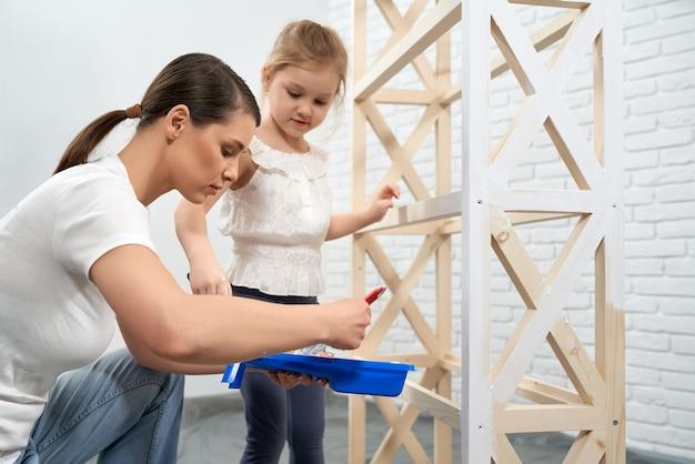 Moeder en dochter die houten rek schilderen