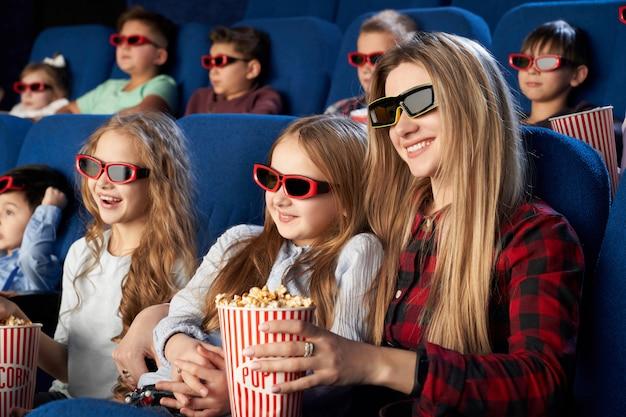Moeder en dochter die in 3d glazen popcorn in bioskoop eten