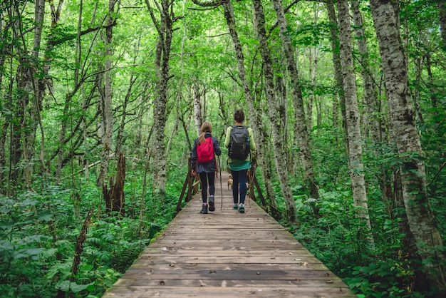 Moeder en dochter die in bos wandelen