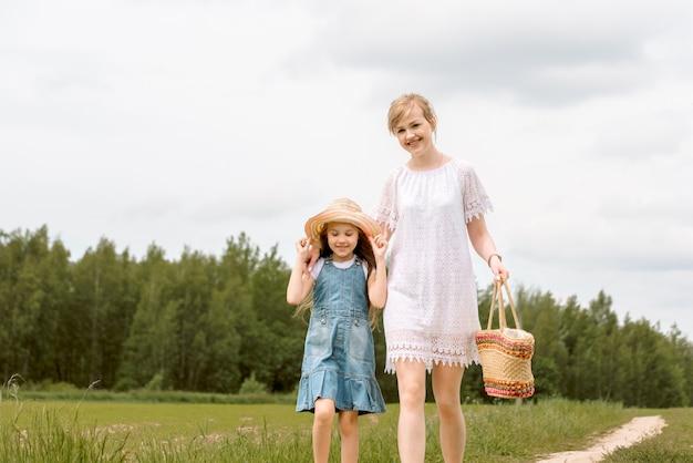 Moeder en dochter die in het bos lopen en handen houden.