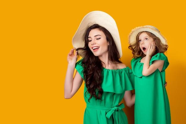 Moeder en dochter die in hoeden omhoog kijken