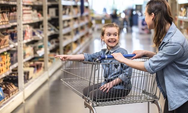 Moeder en dochter die in supermarkt winkelen die producten kiezen