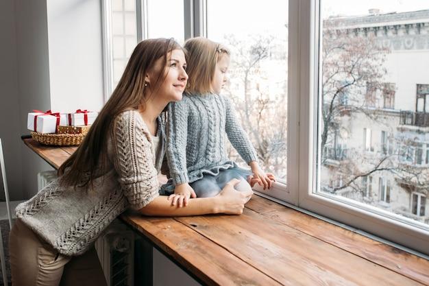 Moeder en dochter die in venster kijken. familie concept.