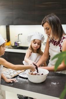 Moeder en dochter die koekjes in keuken maken