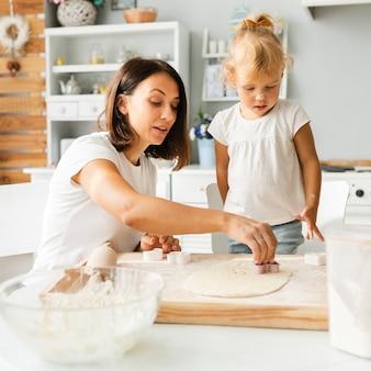 Moeder en dochter die koekjes voorbereiden