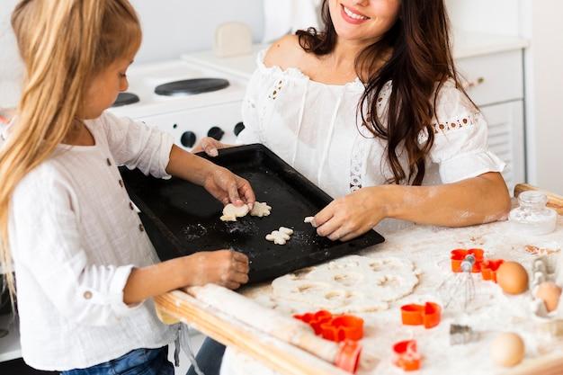 Moeder en dochter die koekjes voorbereidingen treffen te bakken