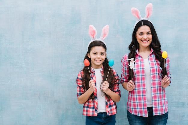 Moeder en dochter die konijntjesoren dragen die paaseieren en konijntjessteunen houden