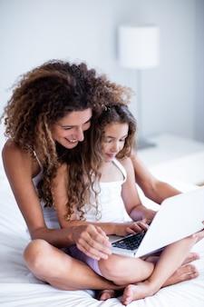 Moeder en dochter die laptop op bed met behulp van