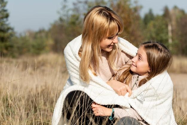 Moeder en dochter die met een deken behandelen