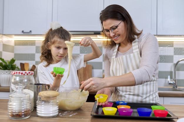 Moeder en dochter die muffins samen in huiskeuken koken. vrouw en kind gieten rauw deeg in siliconen mallen. moederdag, familie, zelfgemaakt gezond bakken