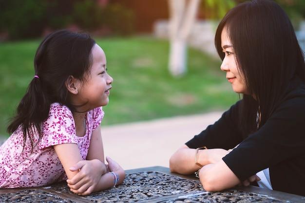 Moeder en dochter die ogen met glimlach en gelukkig kijken.