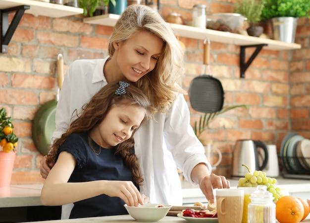Moeder en dochter die ontbijt voorbereiden