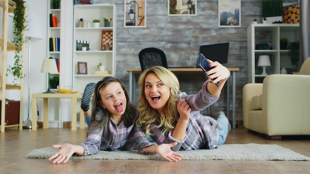 Moeder en dochter die op de vloer liggen en een selfie maken met smartphone.