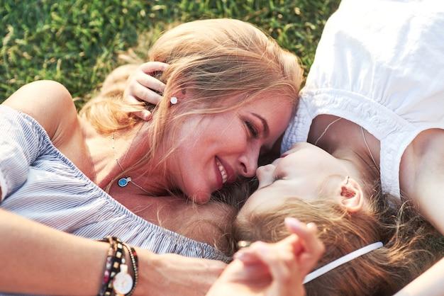 Moeder en dochter die op gras leggen die elkaar aanstaren en glimlachen.