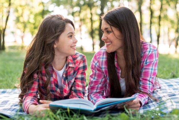 Moeder en dochter die op gras liggen die elkaar bekijken terwijl het houden van boek in park