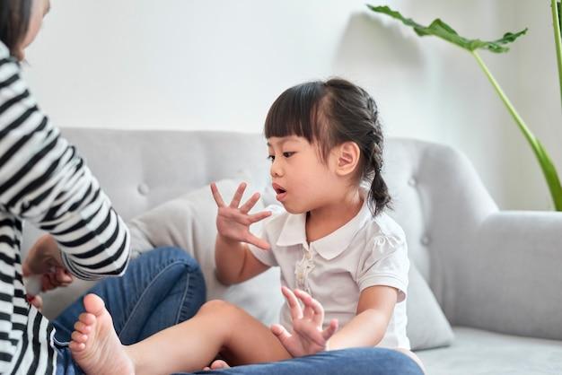 Moeder en dochter die plezier hebben met het schilderen van vingernagels