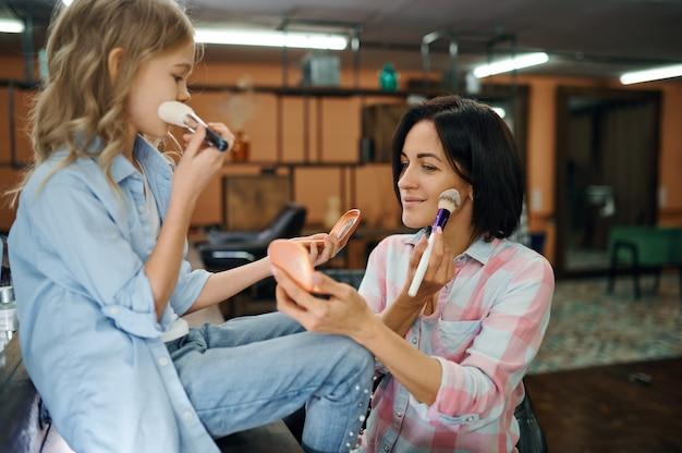 Moeder en dochter die poeder gebruiken in de make-up salon