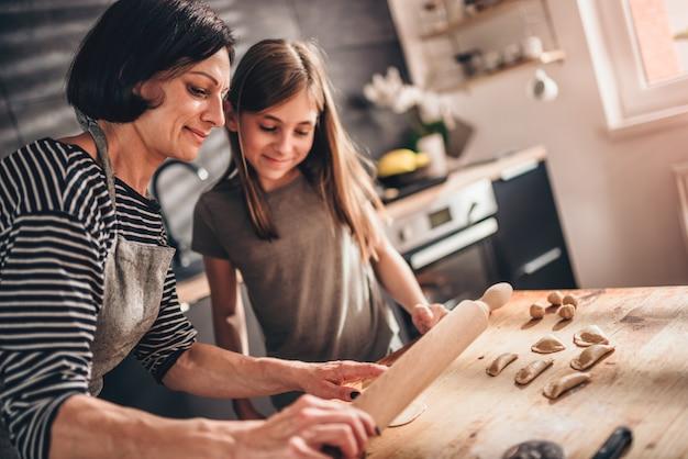Moeder en dochter die ravioli vullen met chocoladeroom