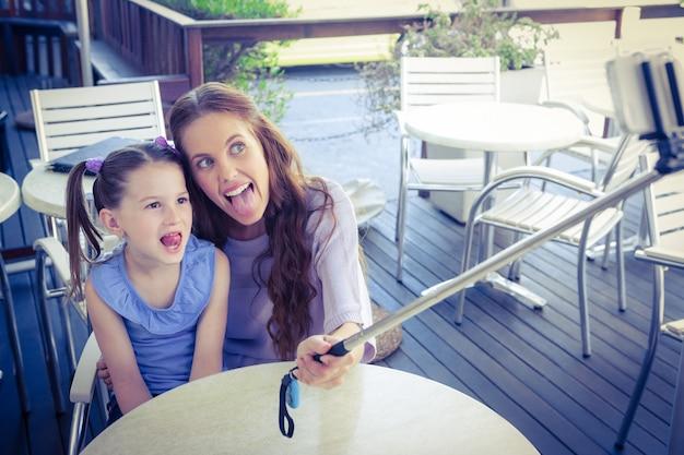 Moeder en dochter die selfiestok gebruiken bij koffieterras