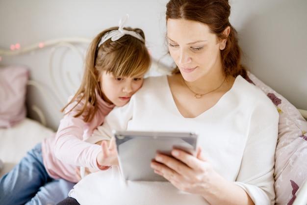 Moeder en dochter die tablet bekijken, die op bed zitten.