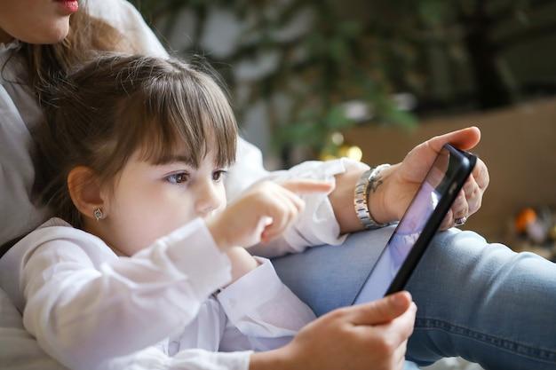 Moeder en dochter die tablet gebruiken