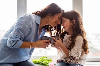 Moeder en dochter die thee op venstervensterbank drinken