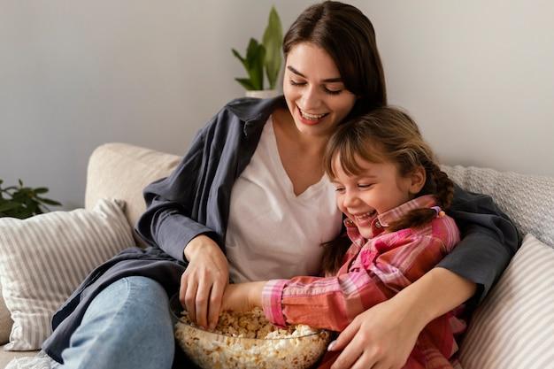 Moeder en dochter die thuis popcorn eten