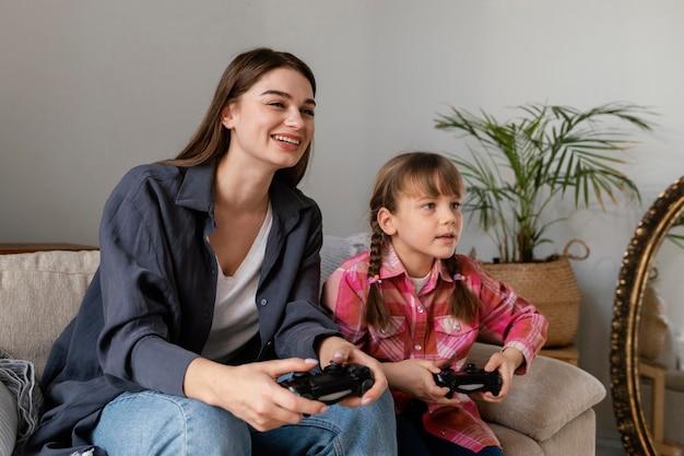 Moeder en dochter die thuis spelletjes spelen