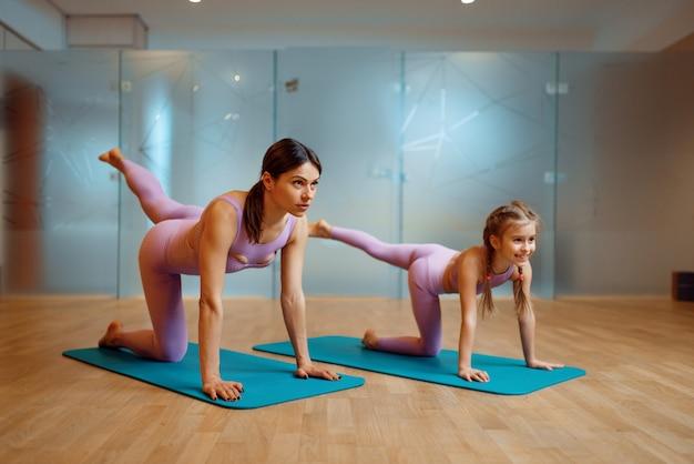 Moeder en dochter die uitrekkende oefening op matten in gymnastiek doen