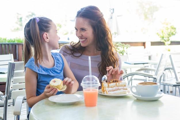 Moeder en dochter die van cakes genieten bij koffieterras