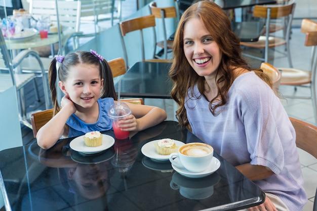 Moeder en dochter die van cakes genieten