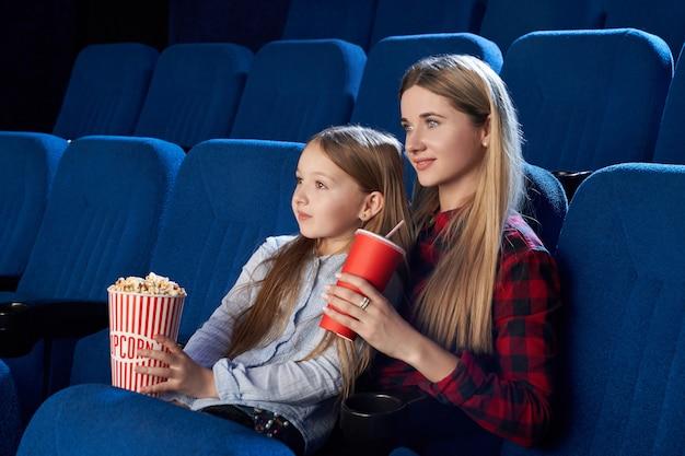 Moeder en dochter die van film in bioscoop genieten.