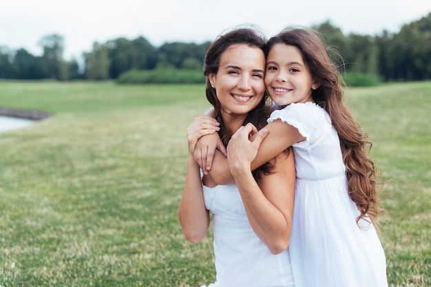 Moeder en dochter die van smiley in openlucht koesteren