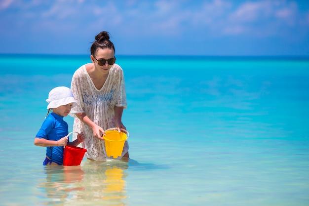 Moeder en dochter die van tijd genieten bij tropisch strand