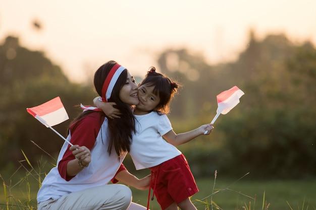 Moeder en dochter die vlag van indonesië opheffen