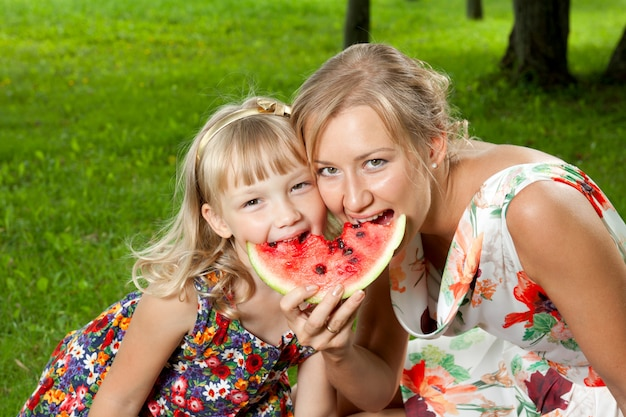 Moeder en dochter die watermeloen eten